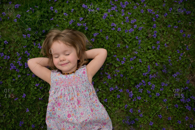 Young girl laying in purple flowers growing in grass