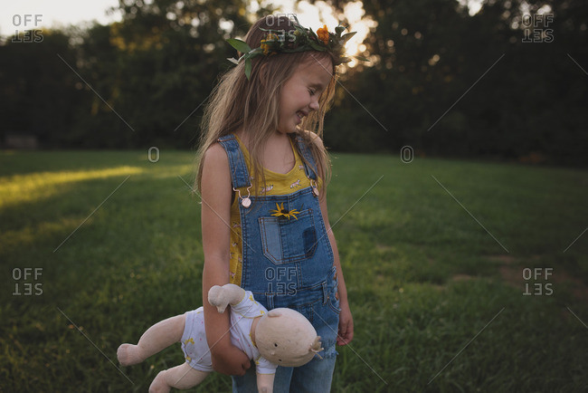 Young girl in overalls holding a doll laughing
