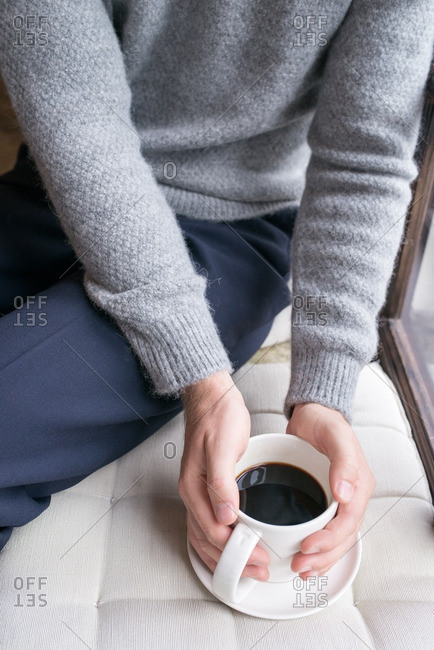 Man sitting near a window holding a cup of coffee