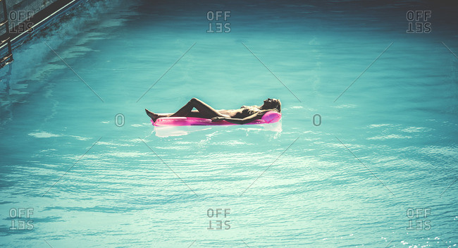 Woman floating on a raft in a swimming pool