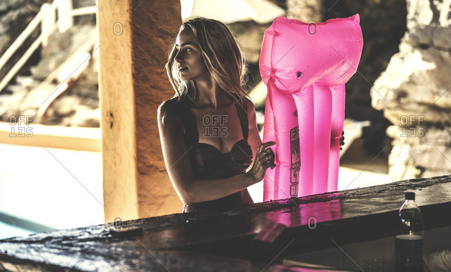 Woman sitting at a poolside bar holding a pink inflatable raft