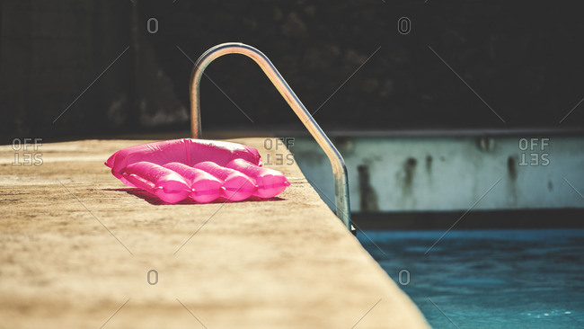 Inflatable pink raft sitting on a swimming pool deck
