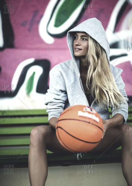 Woman sitting on a bench wearing a hooded sweatshirt and holding a basketball