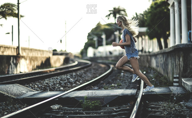 Woman running across train tracks while holding a basketball