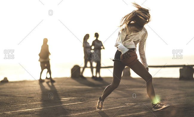 Woman dribbling a basketball on a sunny day