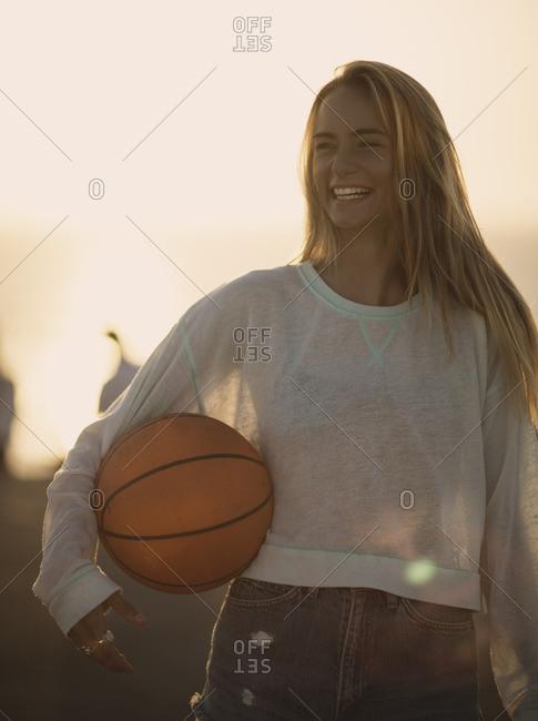 Woman holding a basketball outside on a basketball court
