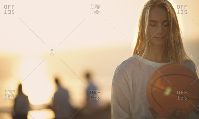 Woman holding a basketball outside