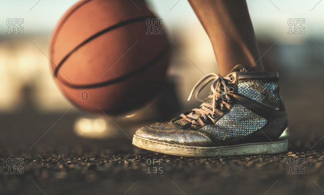 Close-up of a woman's sneakers and a basketball