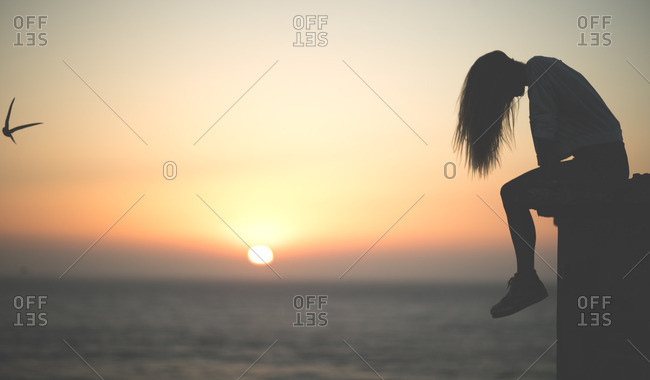 Silhouette of a woman sitting near a beach at sunset