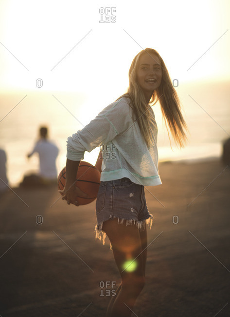 Woman holding a basketball outside on a court