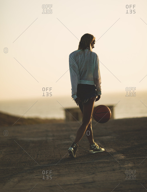 Woman dribbling a basketball behind her back