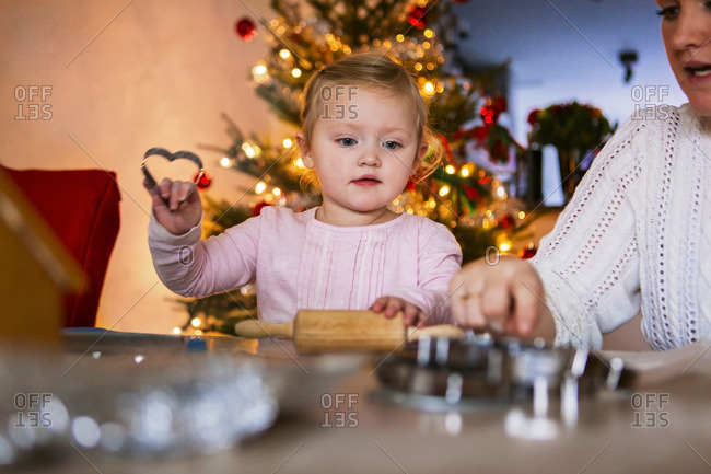 Mother and girl with cookie cutters at table during Christmas