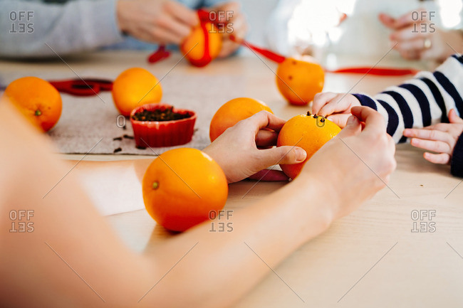 Cropped image of family preparing Christmas decorations at table