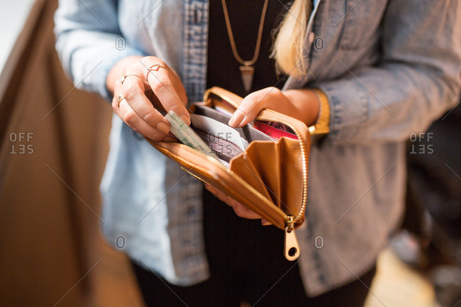 Woman holding open wallet and banknote