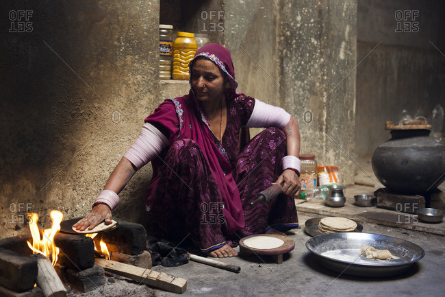 Bisalpur, Uttar Pradesh, India - February 16, 2015: Mid-adult woman making roti, Bisalpur, Uttar Pradesh, India