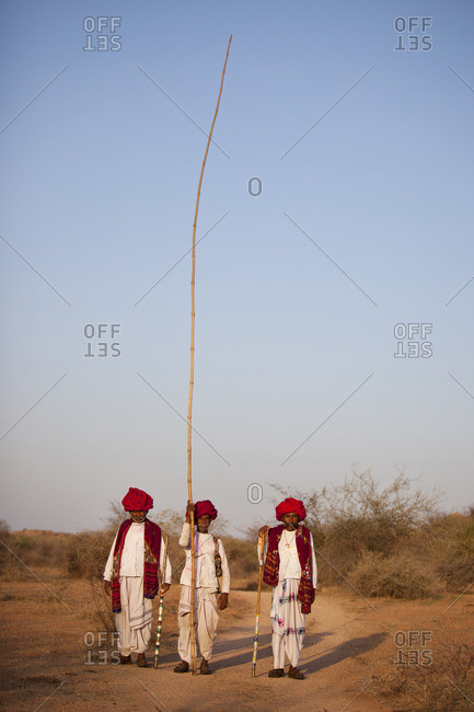 Jawai, Rajasthan, India - March 19, 2015: Rabari men standing with a long stick, Jawai, Rajasthan, India
