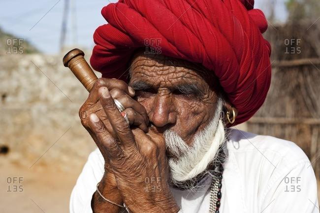 Jawai, Rajasthan, India - April 27, 2015: Close-up of a Rabari smoking a pipe, Jawai, Rajasthan, India