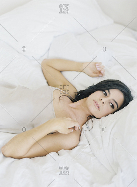 Woman lying in bed in sheer nightgown