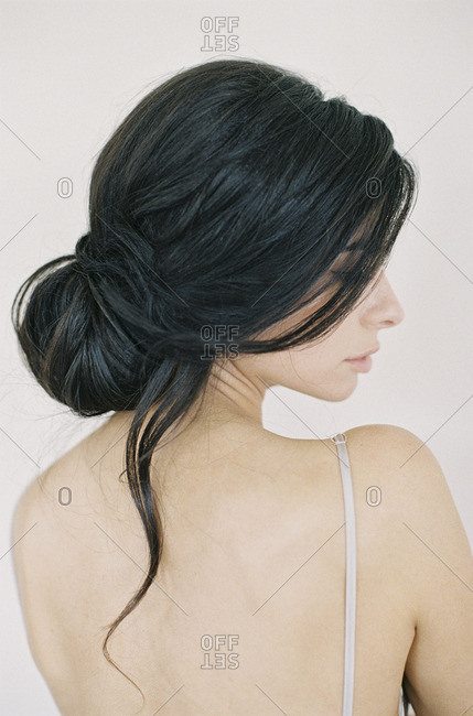 Rear view of woman with dark hair looking over her shoulder