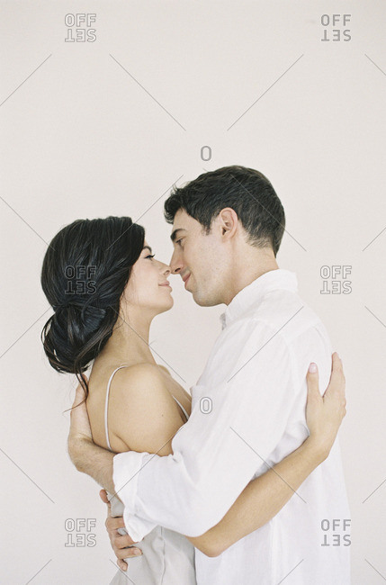 Man kissing woman wearing nightgown