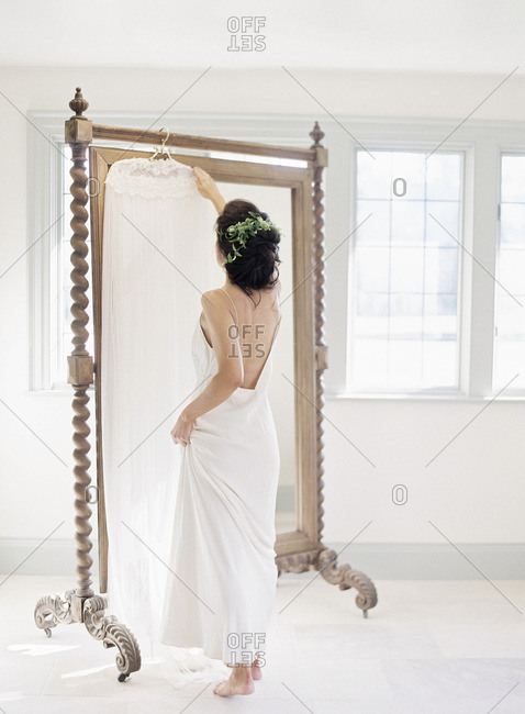 Bride reaching for her wedding dress that is hanging on a mirror