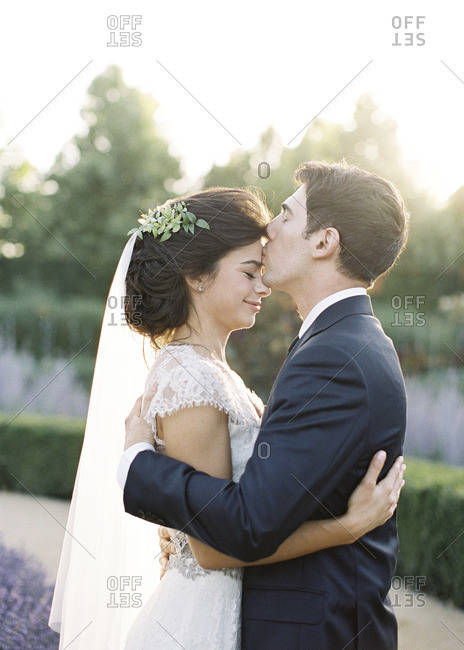 Groom kissing his bride's forehead