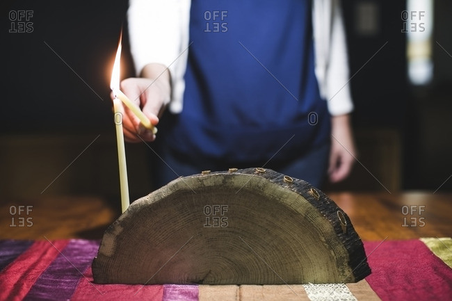 Woman using a candle to light another on a menorah made from a log