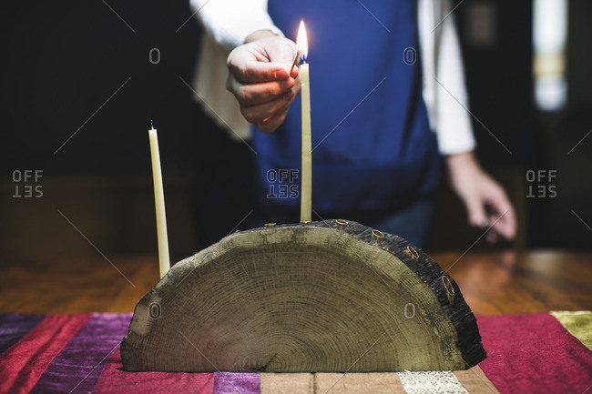 Woman lighting a candle on a menorah made from a log