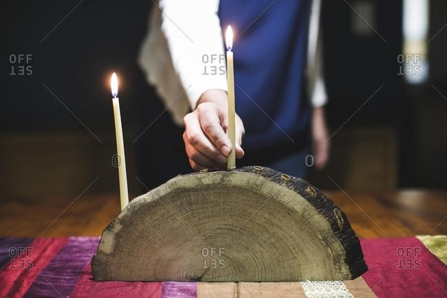 Woman with two lit candles on a menorah made from a log