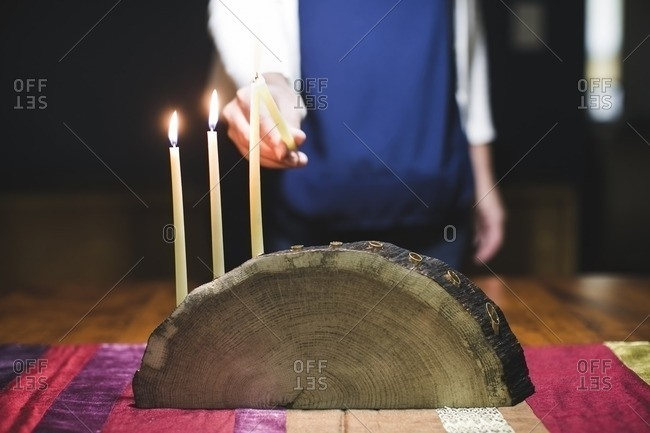 Woman lighting a fourth candle on a menorah made from a log
