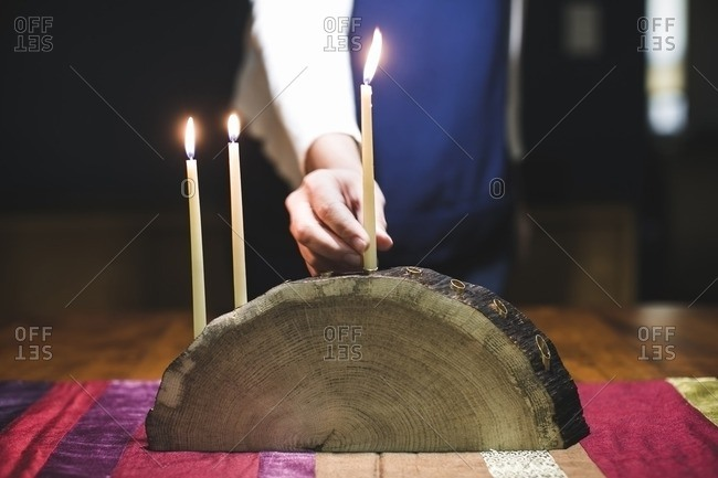 Woman placing a lit candle in the center of a menorah made from a log