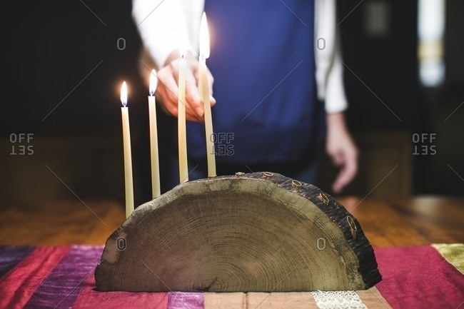 Woman lighting a fifth candle on a menorah made from a log