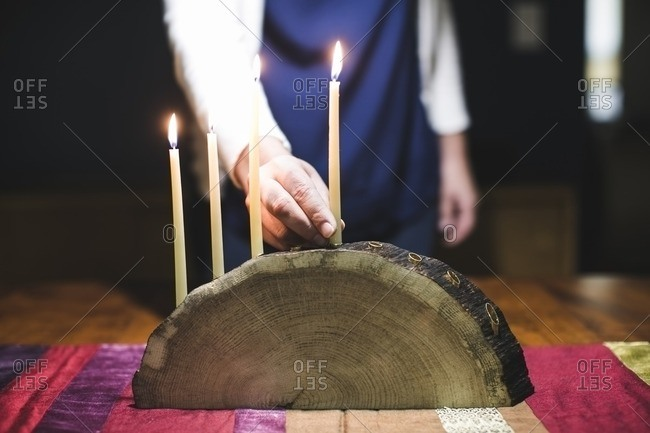 Woman with four lighted candles on a menorah made from a log