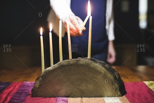 Woman lighting a sixth candle on a menorah made from a log
