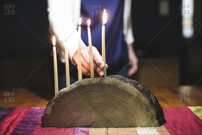 Woman placing a fifth lit candle on a menorah made from a log