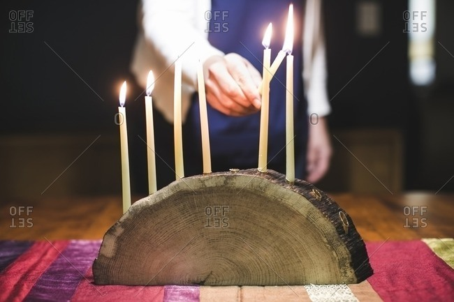 Woman lighting a seventh candle on a menorah made from a log