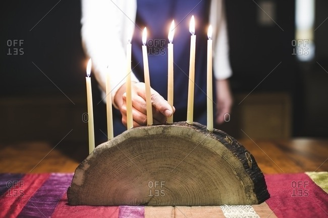 Woman placing a seventh lit candle on a menorah made from a log