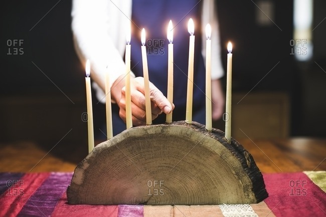 Woman placing an eighth lit candle on a menorah made from a log