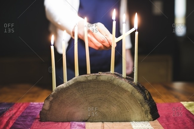 Woman lighting an eighth lighted candle on a menorah made from a log