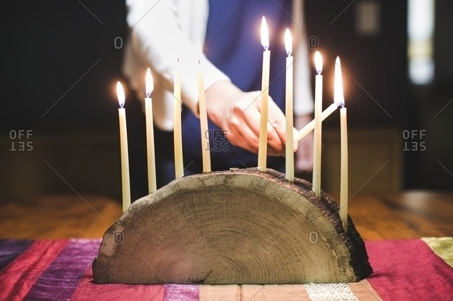 Woman lighting a ninth and final candle on a menorah made from a log
