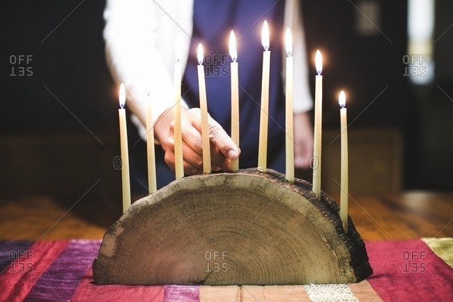 Woman placing a candle in the center of a menorah made from a log