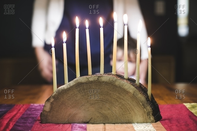 Woman and her son looking at a menorah made from a log with lighted candles