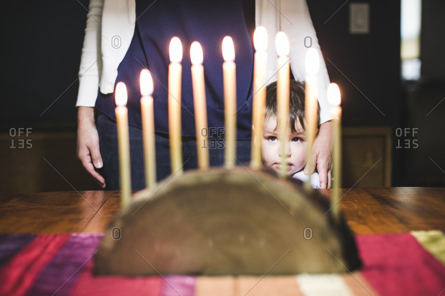 Boy standing with his mother looking at a lighted menorah made from a log