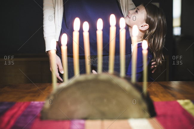 Mother and daughter standing in front of a lighted menorah made from a log