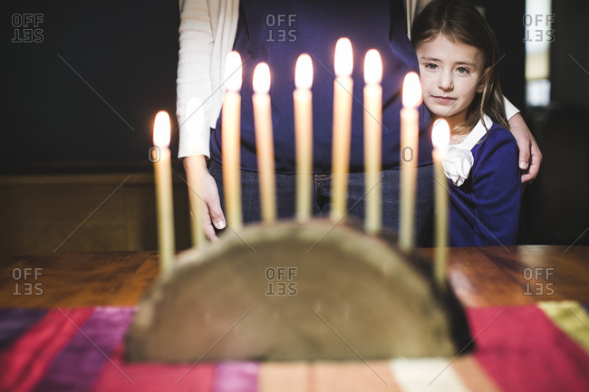 Girl standing with her mother looking at a lighted menorah made from a log