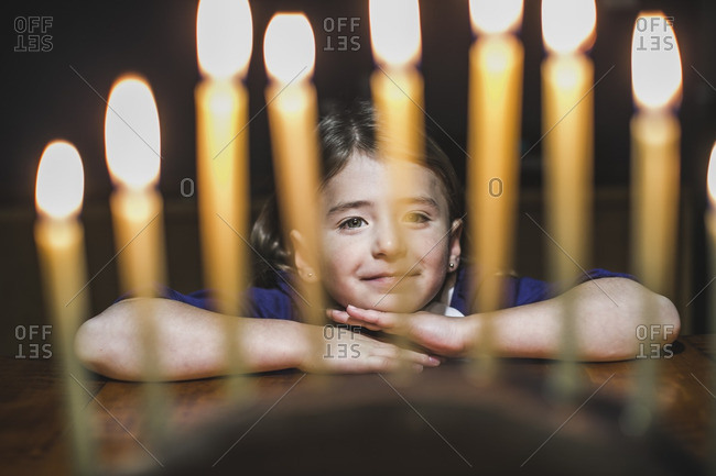 Little girl resting her head on a table looking at a lighted menorah