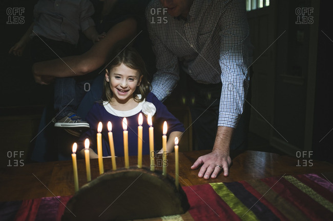 Family standing at a table admiring a menorah made from a log