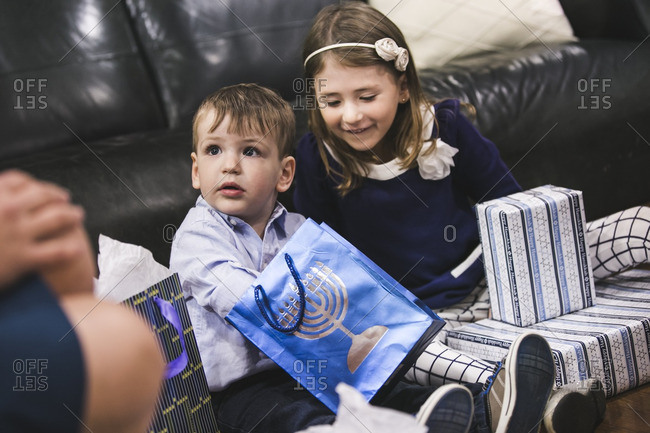 Brother and sister sitting on a living room floor opening Hanukkah presents