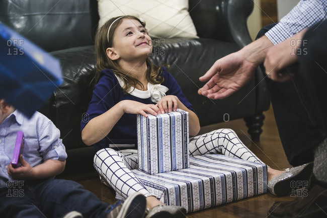 Little girl sitting on a living room floor opening Hanukkah presents