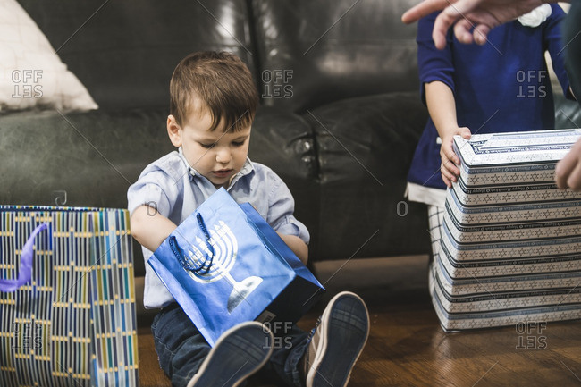 Little boy sitting on a floor opening a gift for Hanukkah